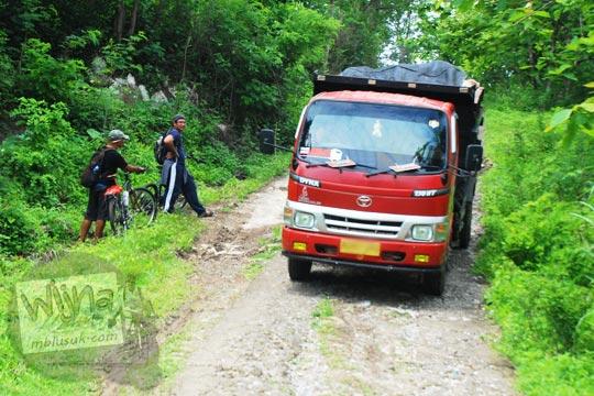 Jalan desa kecil di hutan dilewati truk batu jadinya rusak di Ngelosari, Piyungan, Bantul pada Desember 2015
