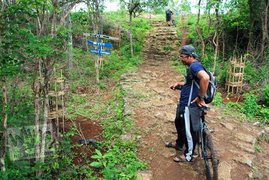 membawa sepeda lewat jalan setapak tanah berbatu becek menuju Puncak Bucu di Desa Srimulyo, Piyungan, Bantul pada Desember 2015