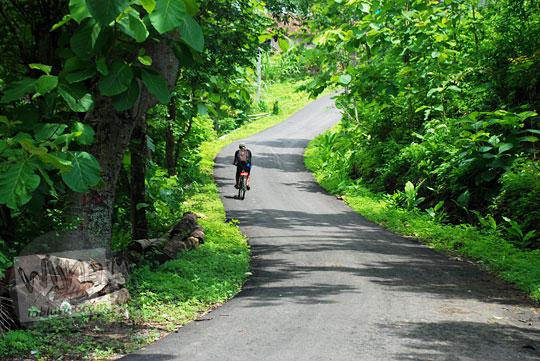 bersepeda melintasi tanjakan di dusun Kaligatuk jalur Wonolelo-Wonosari di Piyungan, Bantul pada Desember 2015