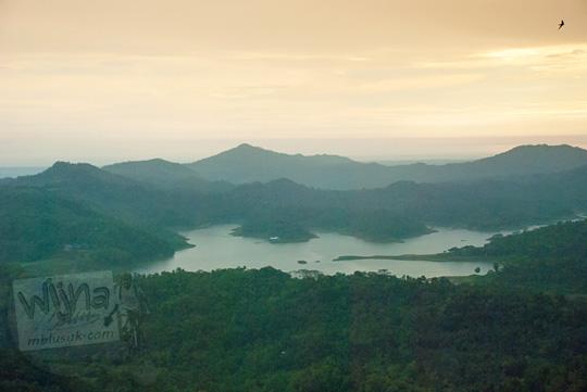 Pemandangan indah Waduk Sermo, Kulon Progo dari ketinggian puncak bukit spot foto pohon obyek wisata Kalibiru pada Januari 2016