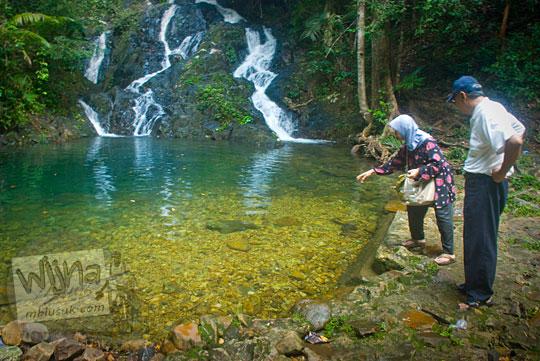 banyak wisatawan lokal mancanegara memberi makan berbagai jenis spesies ikan keramat sakral hidup dasar kolam angker makhluk halus penunggu obyek wisata air terjun gurok beraye belitung