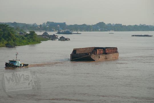 kapal pengangkut batubara melintas sungai batanghari pada pagi hari