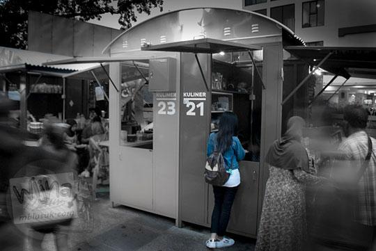 gadis baju biru berdiri di salah satu kedai kuliner teras cihampelas memesan makanan