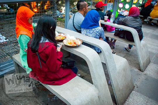 seorang gadis merah bersama ibunya menikmati makanan di teras cihampelas di bangku dan meja batu