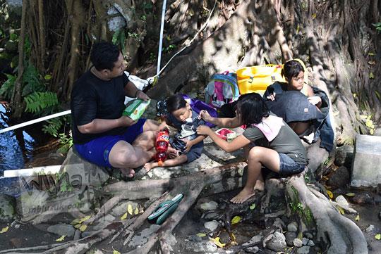foto keluarga bapak ibu dua anak sedang piknik memakan bekal di bawah akar pohon rindang umbul manten tulung klaten jawa tengah