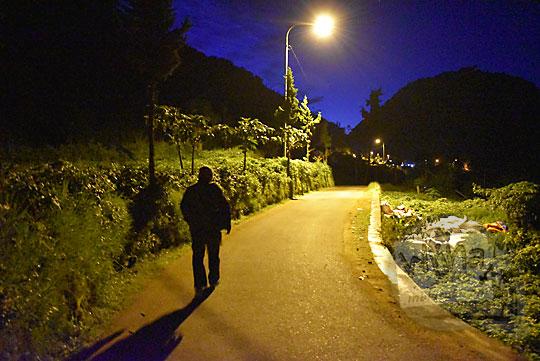 seorang cowok berjaket berjalan kaki di pagi buta di bawah temaram lampu sepi dari Desa Sembungan menuju Bukit Sikunir Dieng di Wonosobo Jawa Tengah