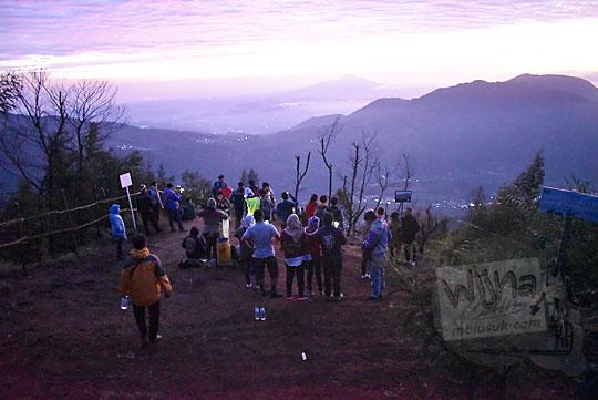 suasana di gardu pandang puncak Sikunir Dieng pada pagi hari sebelum sunrise banyak anak-anak muda cewek mahasisiwi cantik berkumpul