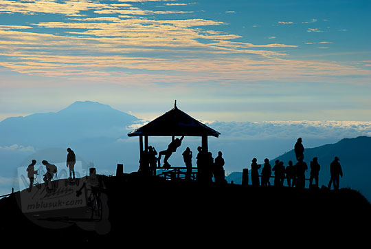 siluet aktivitas pengunjung cewek-cowok bergaul bebas di gardu pandang puncak tertinggi Bukit Sikunir Dieng