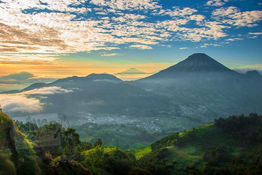 pemandangan sunrise suasana pagi gunung sindoro dengan foreground semak hutan hijau alami dari puncak Bukit Sikunir Dieng