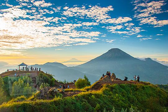 pemandangan sunrise suasana pagi gunung sumbing dengan latar siluet aktivitas pengunjung dari puncak Bukit Sikunir Dieng
