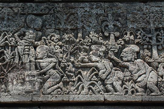 relief arjuna berkelahi dengan batara guru memperebutkan hak atas babi hutan yang dibunuh dengan panah disaksikan punakawan sesuai kakawin arjunawiwaha, di Candi Surowono, Kediri