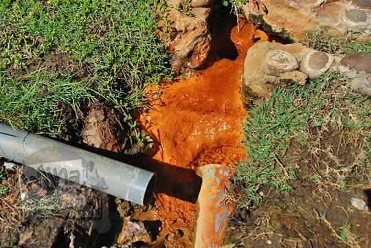foto penampakan aliran air panas berbau belerang di tanah halaman candi songgoriti