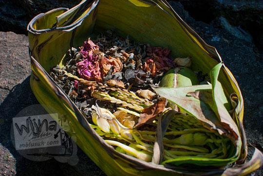 anjuran memberikan sesaji berupa beras atau padi disertai kembang tujuh rupa di candi songgoriti