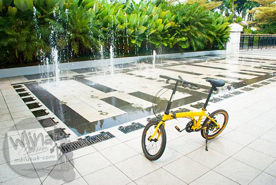 sepeda lipat kuning di depan air mancur di luar gerbang balai kota Surabaya