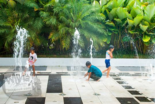 anak-anak bermain air mancur di depan balai kota Surabaya