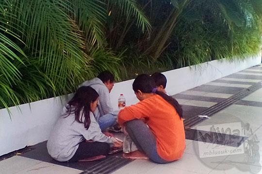 foto keluarga piknik makan bekal rujak cingur duduk di trotoar depan balai kota Surabaya