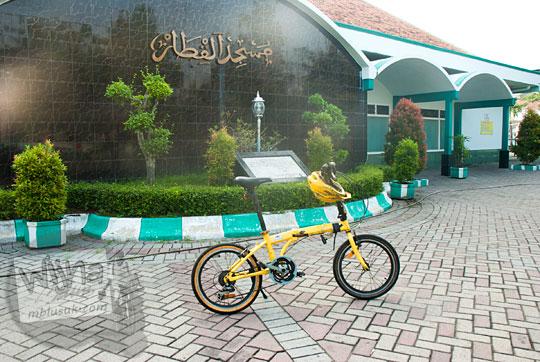 sepeda lipat warna kuning di area parkir majid Al-Qithaar Kota Surabaya dekat Stasiun Gubeng