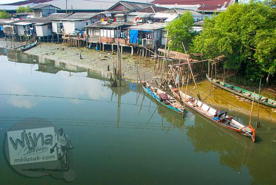 pemandangan rumah nelayan pinggir sungai ada perahu ditambat di pinggir jalan raya Surabaya Gresik