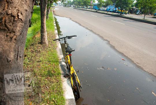 bersepeda lipat lewat genangan air comberan di jalan raya Surabaya Gresik