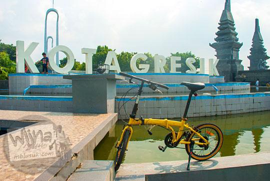 sepeda lipat warna kuning di tugu selamat datang kota Gresik