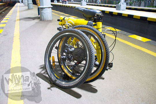 sepeda lipat polygon bike2work warna kuning di peron stasiun tugu malam hari