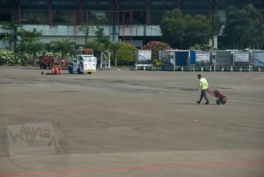 petugas groundcrew membawa tabung pemadam di bandara soekarno-hatta