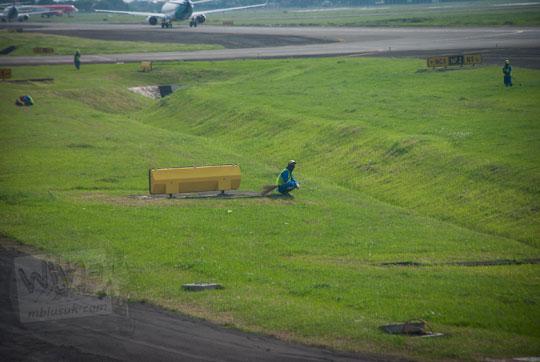 petugas kebersihan rumput beristirahat di bandara soekarno-hatta