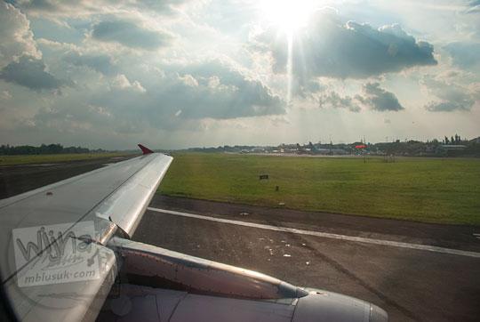 pemandangan landing pesawat di bandara adisucipto dari jendela