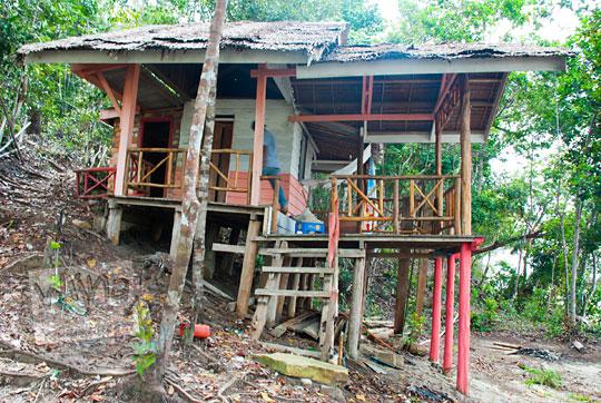 kedai warung kayu sederhana berbentuk rumah panggung terbengkalai tidak berpenghuni berhantu di Pantai Moyang di Pulau Lingga Kepulauan Riau