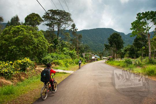 suasana anak sd bersepeda di jalan raya desa di pulau lingga kepulauan riau