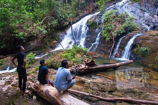 wisatawan menikmati tebing indah puncak air terjun resun lingga di kepulauan riau