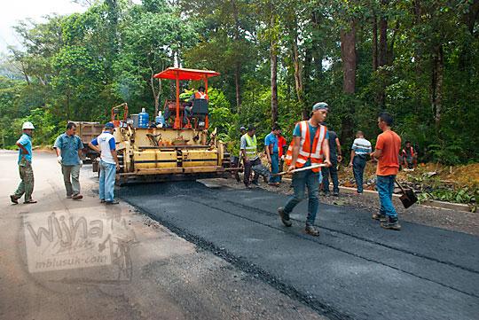foto suasana aktivitas kegiatan pengerjaan proyek pengaspalan jalan raya di pulau lingga kepulauan riau