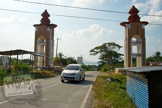 jenis jadwal angkutan transportasi umum yang lewat gapura simpang tiga batu bersurat ke arah Candi Muara Takus, Kampar, Riau pada April 2016