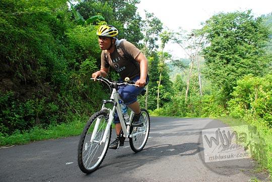 cowok naik sepeda mtb nanjak samigaluh hutan kulon progo