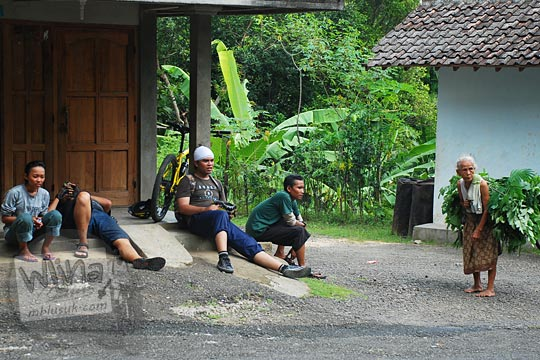 orang pendatang duduk teras rumah disapa warga tua simbah bawa daun pakan ternak