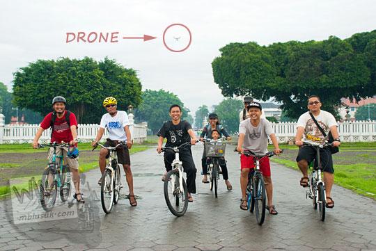 foto asyiknya bersepeda ramai-ramai melewati beringin kembar alun-alun utara keraton yogyakarta direkam dengan drone terbang di udara