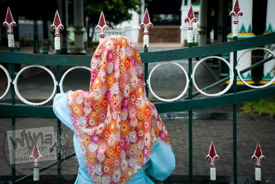 seorang wanita berjilbab misterius menunggu seseorang dari balik gerbang keraton yogyakarta