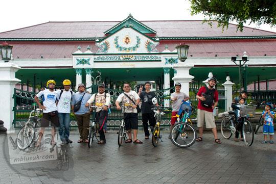 foto pesepeda bergaya berdiri dengan sepeda di depan gerbang masuk keraton yogyakarta di alun-alun utara