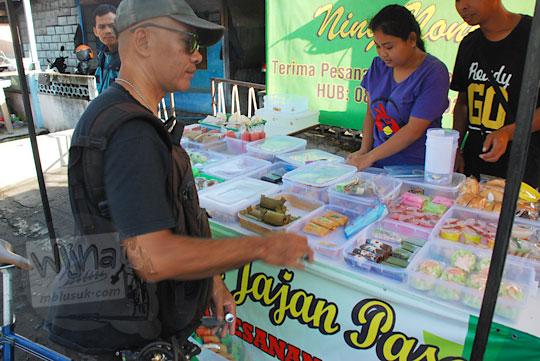 pria kaos hitam sedang membeli jajanan pasar di kios pasar tanjungtirto berbah sleman jogja