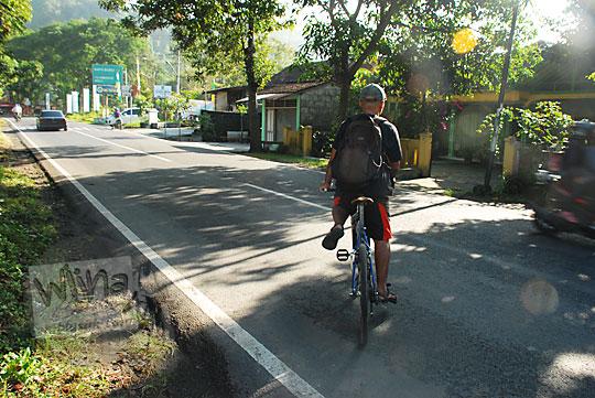 pria kaos hitam bersepeda tengah jalan raya prambanan piyungan yogyakarta