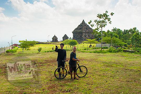 dua pesepeda dengan kaos hitam berfoto bareng di halaman luar candi ijo