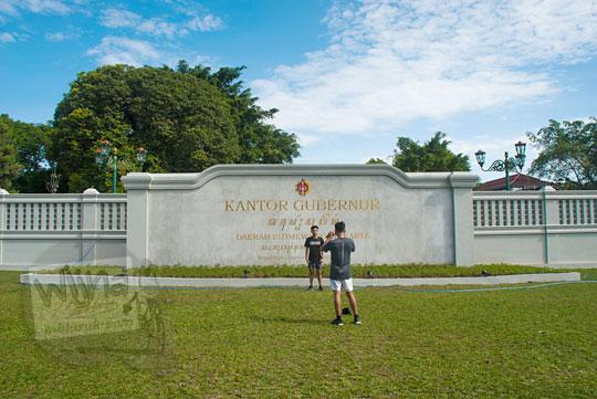 dua orang pemuda sedang berfoto di depan plakat baru nama kompleks kepatihan danurejan