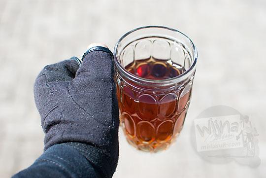 foto tangan cowok sarung tangan hitam memegang segelas teh hangat