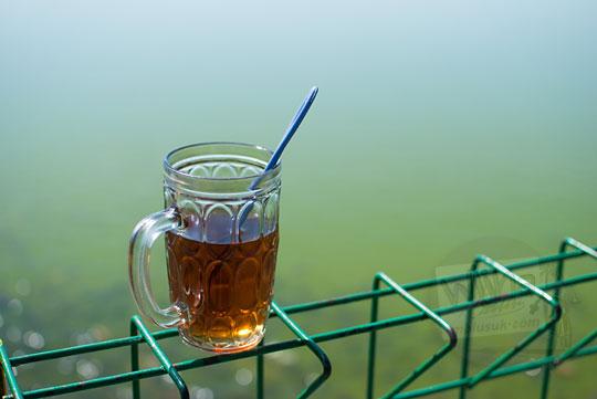 foto segelas teh hangat di atas pagar embung tonogoro di banjaroya kalibawang kulon progo