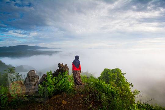 cewek berjilbab merah berdiri menatap lautan kabut di puncak Bukit Turunan di Girisuko Panggang Gunungkidul Yogyakarta pada zaman dulu Desember 2017
