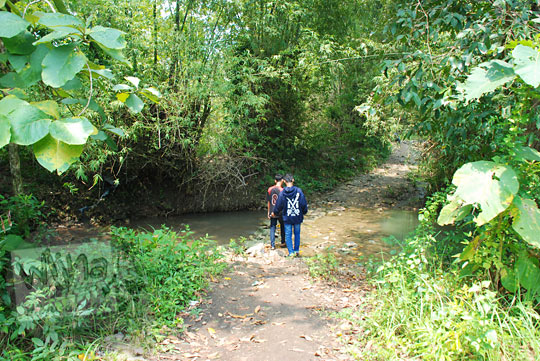 wisatawan cowok siswa-siswi sma berjalan kaki menyeberang sungai menuju air terjun bangunsari semin candirejo gunungkidul