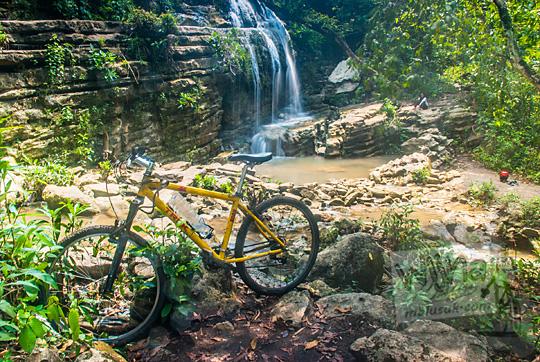 foto sepeda kuning dengan latar belakang curug bangunsari semin candirejo gunungkidul