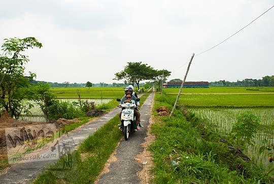 sepeda motor melintasi jalan pematang sawah yang asri di kecamatan weru sukoharjo jawa tengah