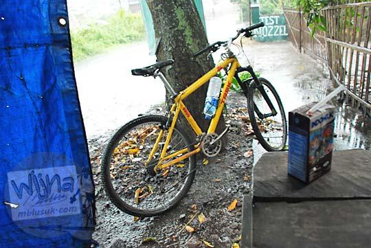 sepeda kuning berteduh dari hujan deras di dalam angkringan sekitar wilayah bayat jawa tengah