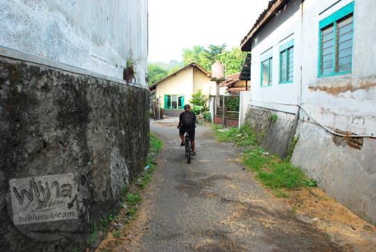 orang bersepeda di antara rumah warga di kecamatan Piyungan, Bantul yang terdesak terkepung oleh pabrik-pabrik